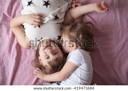 sibling relationships, children's secrets, hug, close up, domestic real situation, the concept of childhood, lifestyle,toning, - stock photo