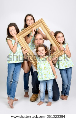Siblings and dad posing with a frame