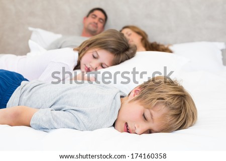 Siblings and parents sleeping in bed - stock photo