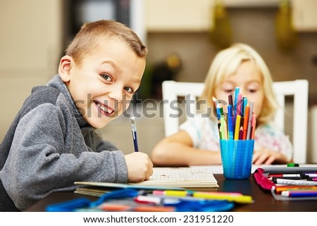 Siblings are doing his homework for elementary school. - stock photo