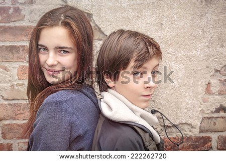 siblings back to back in front of an old brick wall - stock photo
