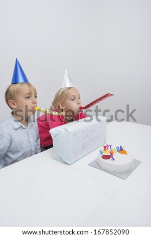 Siblings blowing noisemakers at birthday party in house - stock photo