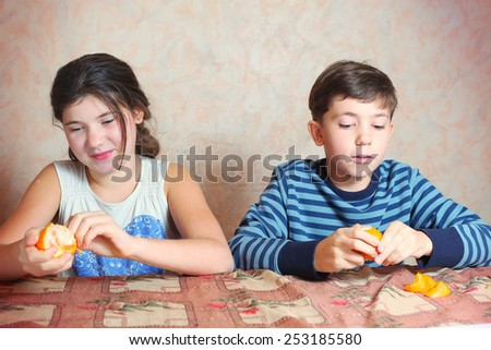 siblings boy and girl compete who  peel tangerine quicker - stock photo