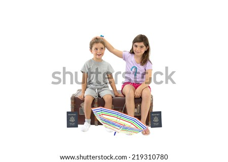 Siblings (boy silly face, girl looking at camera) sitting on vintage luggage with US passports and umbrella isolated on white background
