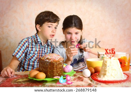 siblings brother and sister decorate egg and easter cake for easter dinner - stock photo