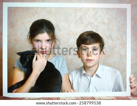 siblings brother and sister with black cat cute portrait in frame - stock photo