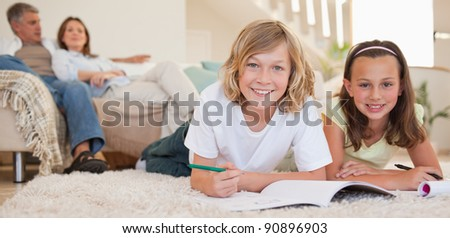 Siblings doing their homework on the floor with their parents behind them - stock photo