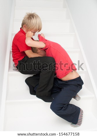Siblings fighting on the stairs in the home.
