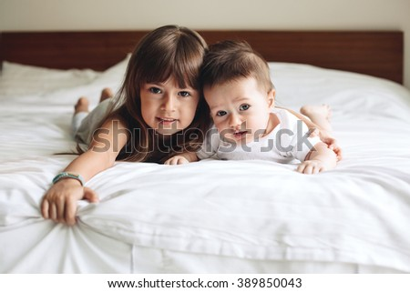 Siblings hugging and laying down on the bed in bedroom