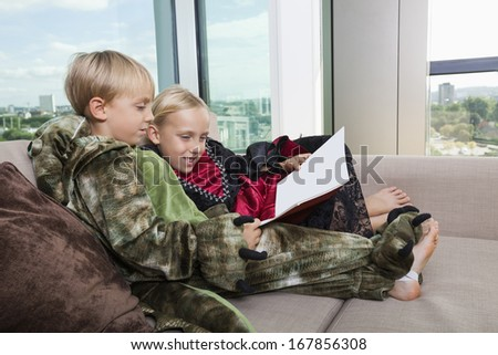 Siblings in dinosaur and vampire costumes reading picture book together on sofa bed at home - stock photo