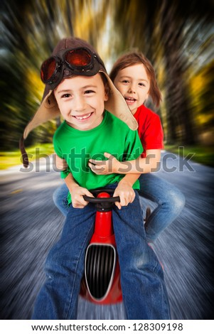 Siblings in retro racing hat and goggles driving on toy car at speed with blurred background.