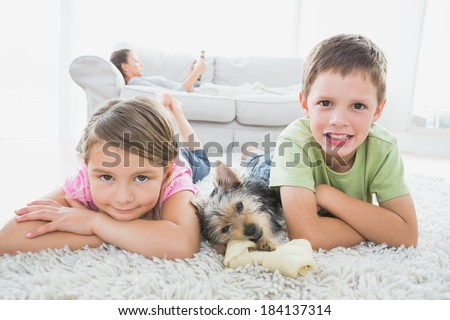 Siblings lying on rug with yorkshire terrier smiling at camera at home in the living room - stock photo
