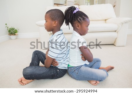 Siblings not talking to each other at home in the living room - stock photo