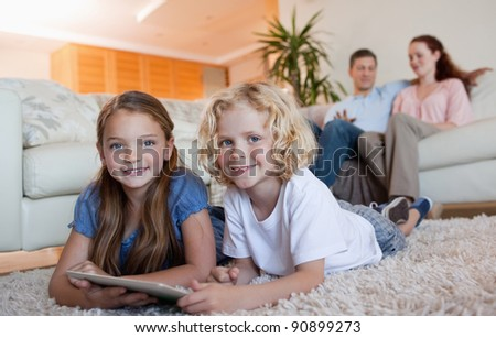 Siblings on the carpet using tablet together - stock photo