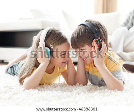 Siblings playing on the floor with headphones in the living room - stock photo