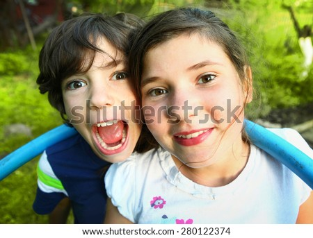 siblings preteen boy and girl together close up portrait on the summer green background