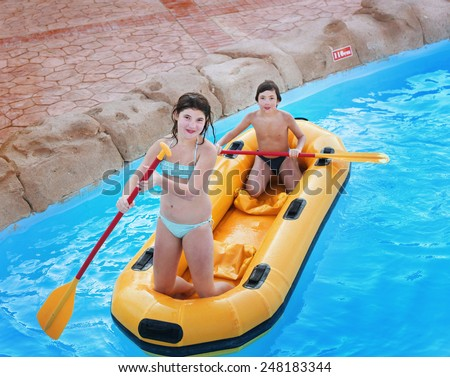 siblings preteen girl and boy in rubber boat with raw in egyptian open air water park - stock photo