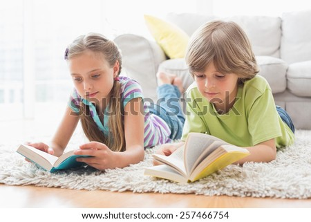 Siblings reading books while lying on rug in living room - stock photo