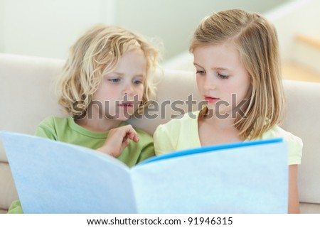 Siblings reading magazine together on the couch