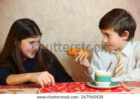 siblings sister and brother are naughty while eat croissant with breakfast tea play and laughing - stock photo