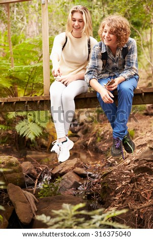 Siblings sitting on a wooden bridge in a forest, vertical - stock photo