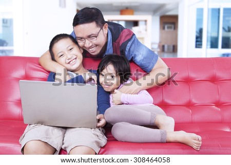 Siblings sitting on sofa  shopping online with their dad at home - stock photo