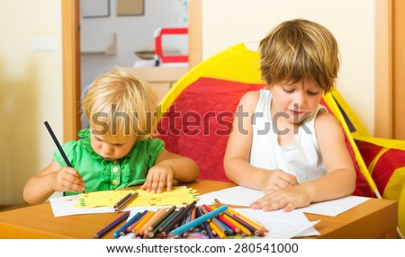 Siblings  sketching on paper in home interior - stock photo