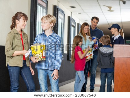 Siblings talking at cinema with family and worker in background - stock photo