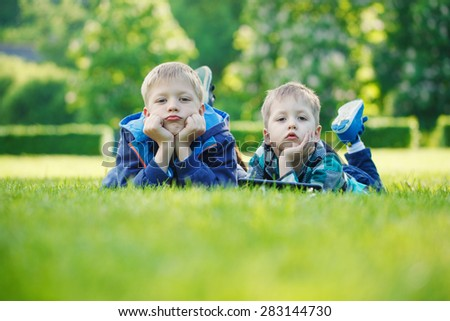 Siblings using a tablet, lying on grass in the park in sunny day