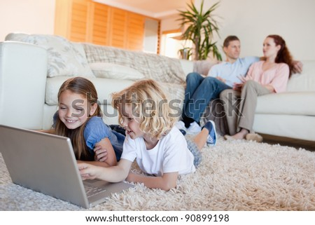Siblings using laptop in the living room together - stock photo