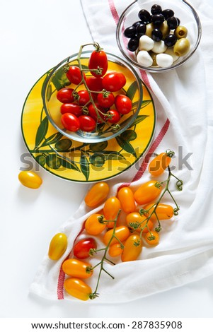 Sicilian red and yellow cherry tomatoes, green and black olives, fresh basil leaves. Summer Italian ingredients. - stock photo
