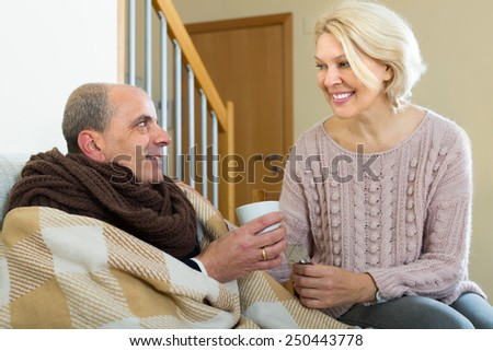 Sick aged man with cold taking pill from caring woman - stock photo