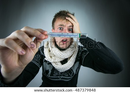 Sick and tired man with clinical thermometer. Cold man. Man looks at the clinical thermometer. Man in a fever