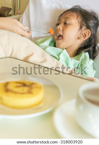 Sick Asian Ethnic Little Girl Hospital Patient Having Meal on Bed Helped by Mother - stock photo