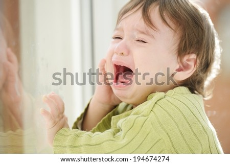 Sick baby standing and waiting on window glass - stock photo