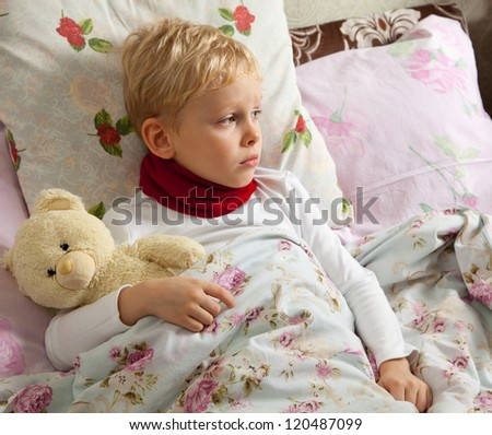 Sick boy is laying in bed with his teddy bear.