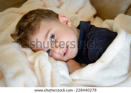 Sick boy under the blanket - stock photo
