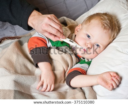 Sick boy with thermometer laying in bed and hand taking temperature