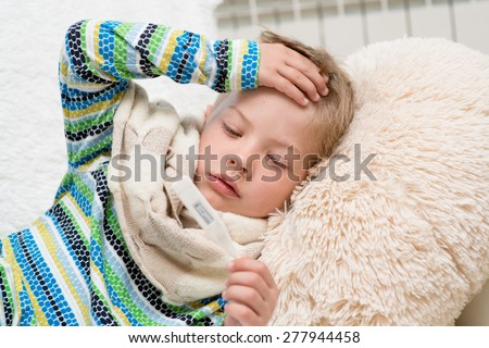 Sick boy with thermometer laying in bed and taking temperature - stock photo