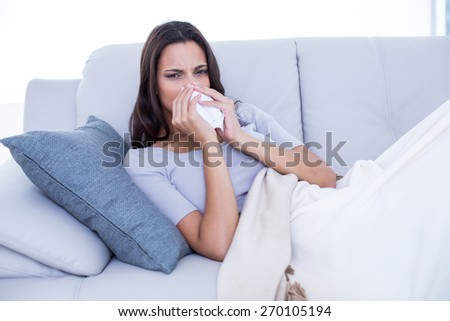 Sick brunette lying on the couch and blowing her nose in the living room - stock photo