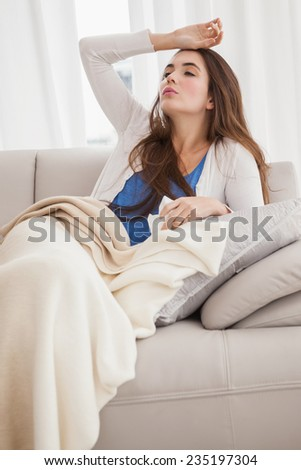Sick brunette on the couch at home in the living room