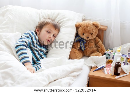 Sick child boy lying in bed with a fever, resting at home - stock photo