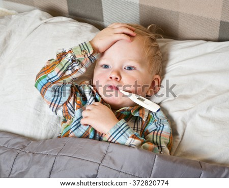 sick child boy lying in bed with a thermometer in mouth and touch his forehead - stock photo