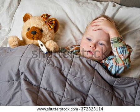 sick child boy lying in bed with toy bear and thermometer in mouth - stock photo