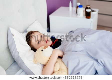 Sick child hugging a teddy bear in bed.