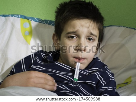 Sick child in bed. Measuring the temperature with a thermometer. - stock photo