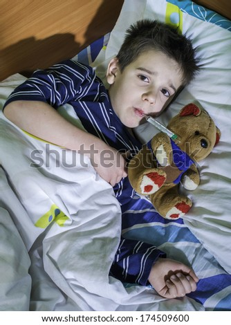 Sick child in bed with teddy bear. Measuring the temperature with a thermometer. - stock photo