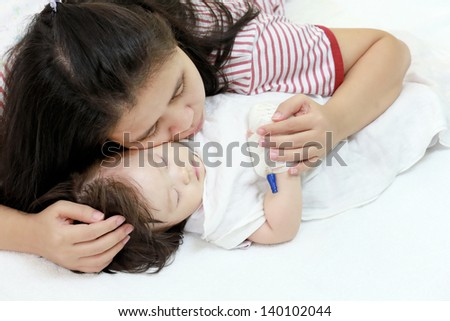 Sick child in her mother's arms. - stock photo