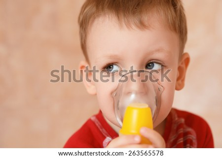 Sick child makes himself inhalation mask for breathing at home - stock photo