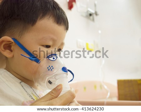 Sick child wearing inhalation mask for breathing treatment.